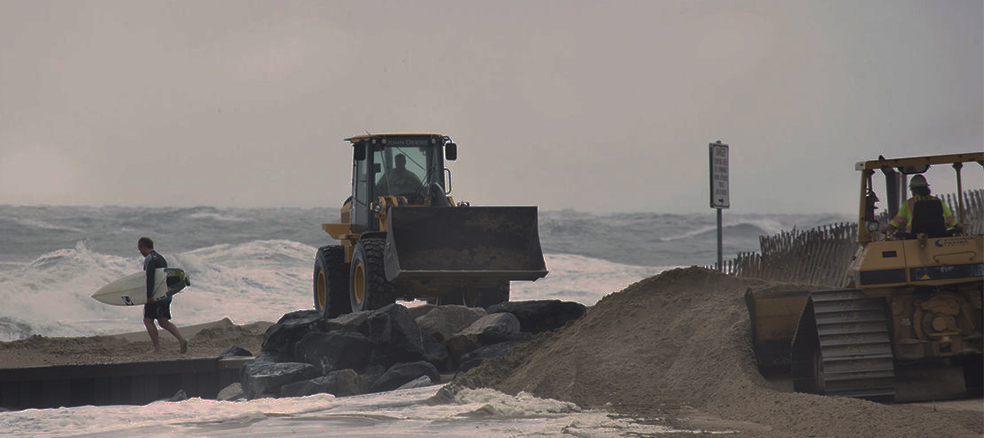 wheel loaders moving sand on the beach during a hurricane while a surfer walks by